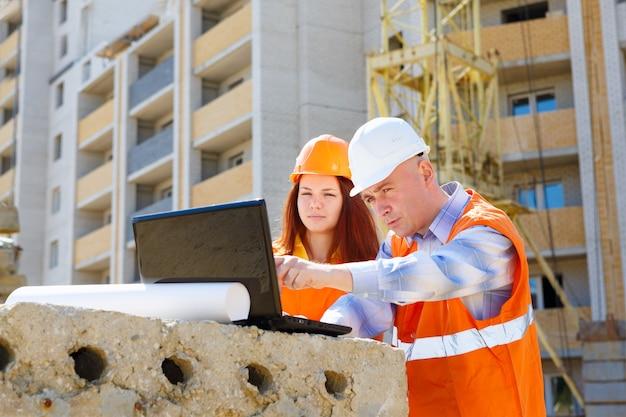 Trabalhadores da construção civil femininos e masculinos olhando para o laptop