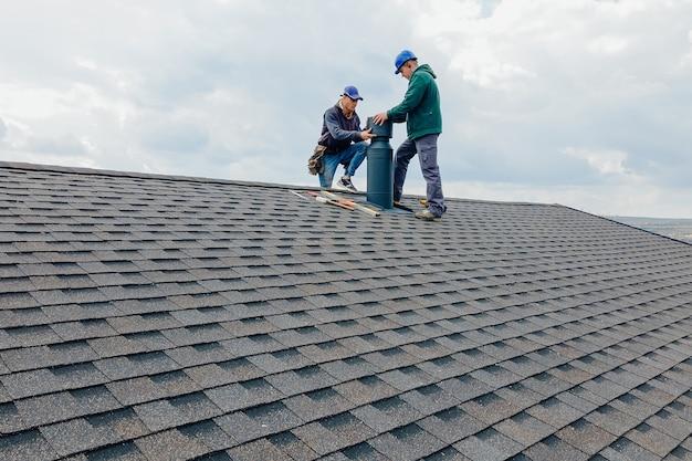 Trabalhadores da construção civil instalando chaminé e construtor de empreiteiro de conceito de construção com capacete azul no telhado para calafetar a chaminé