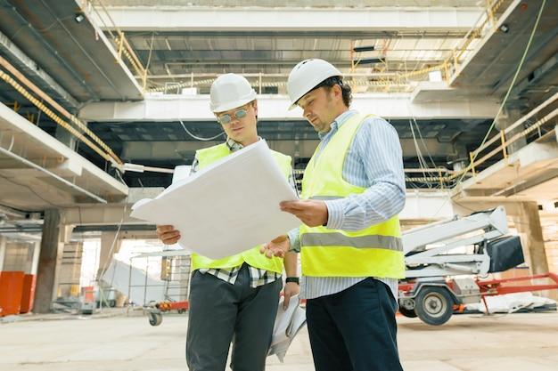 Trabalhadores da construção civil masculino trabalhando no canteiro de obras, construtores olhando na planta