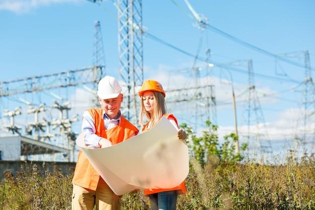 Trabalhadores da construção civil masculinos e femininos no capacete contra projetos elétricos