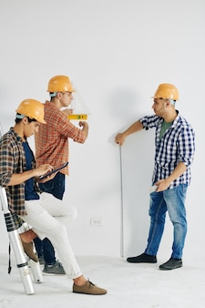 Trabalhadores da construção civil medindo parede com várias ferramentas quando seu colega inserindo dados no documento no computador tablet