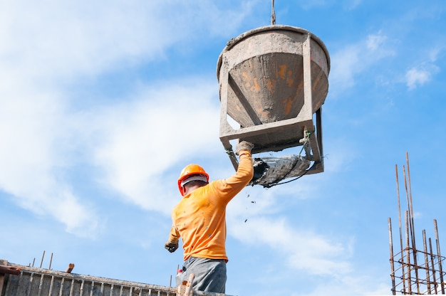 Trabalhadores da construção civil no local da construção despejando concreto na forma, homem trabalhando em altura com céu azul no local da construção