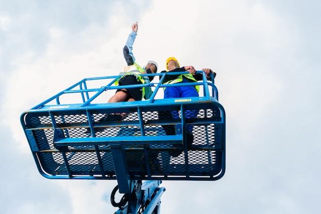 Trabalhadores da construção civil no local em rampa de elevação hidráulica
