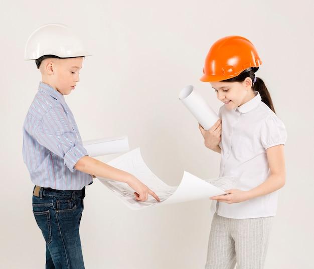 Trabalhadores da construção civil olhando para o projeto