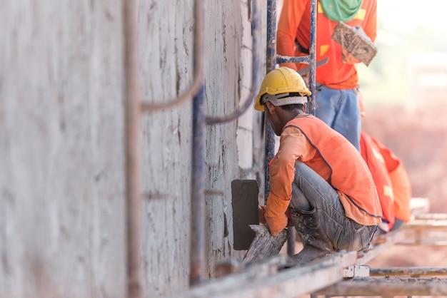 Trabalhadores da construção civil rebocando paredes e vigas do edifício usando mistura de gesso de cimento e areia no local da construção
