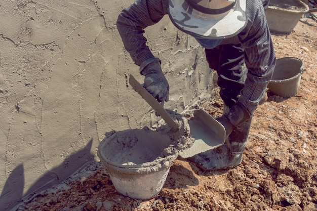 Trabalhadores da construção civil reboco parede do edifício usando cimento gesso