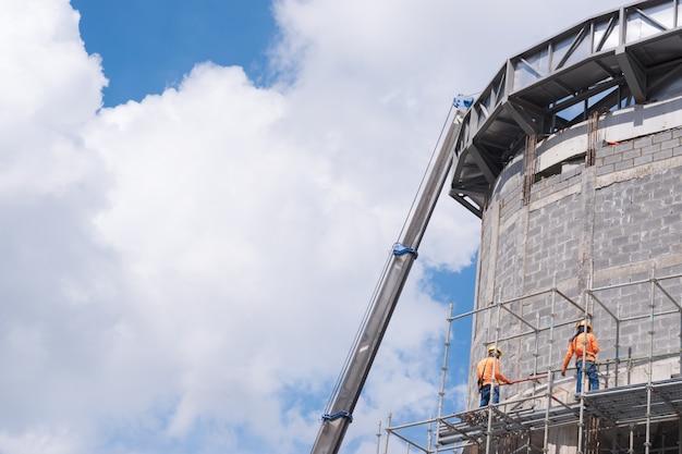Trabalhadores da construção civil trabalhando no topo da estrutura do edifício com céu azul e nuvem branca ba