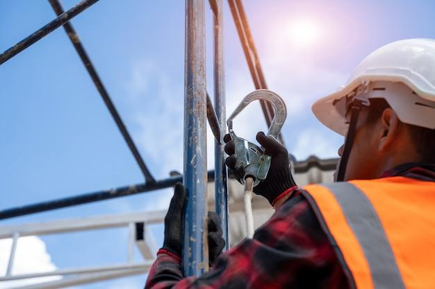 Trabalhadores da construção civil usando arnês de segurança trabalhando em alto nível no canteiro de obras, ferramentas para telhados, furadeira elétrica usada em telhados novos com chapa de metal.