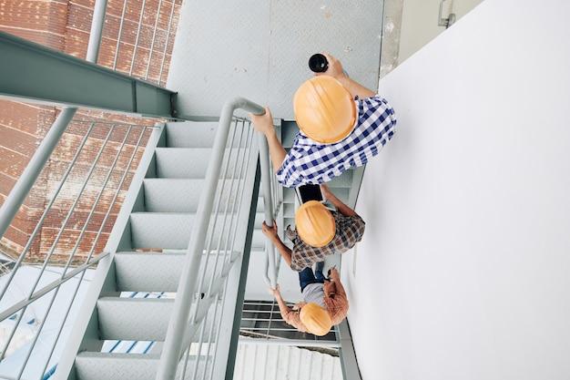 Trabalhadores da construção civil usando capacetes subindo as escadas um após o outro, vista do topo