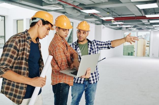 Trabalhadores da construção civil usando laptop