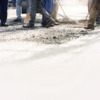 Trabalhadores da construção de estradas que reparam a estrada asfaltada.