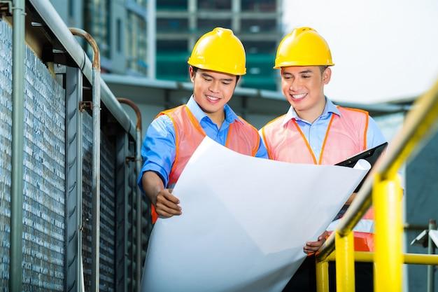Trabalhadores da construção indonésio asiáticos na construção de site