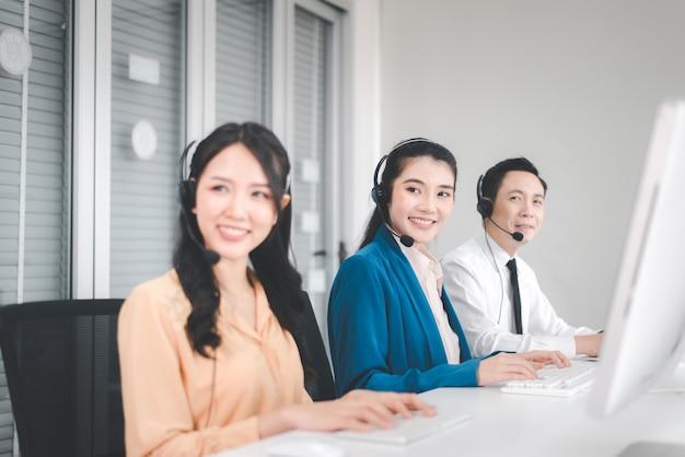 Trabalhadores da equipe asiática do call center juntos no escritório, operadora de mulher sorridente de funcionários trabalhando com fone de ouvido