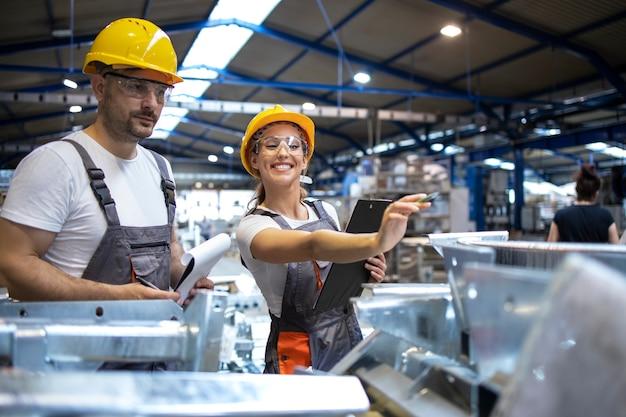 Trabalhadores da fábrica analisando os resultados da produção em um grande salão industrial