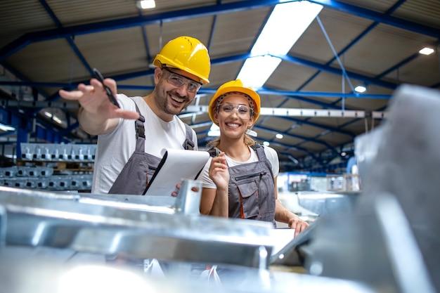 Trabalhadores da fábrica controlando a qualidade dos produtos manufaturados juntos