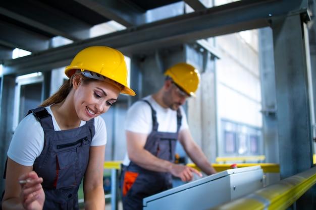 Trabalhadores da fábrica monitorando máquinas industriais e produção remotamente na sala de controle