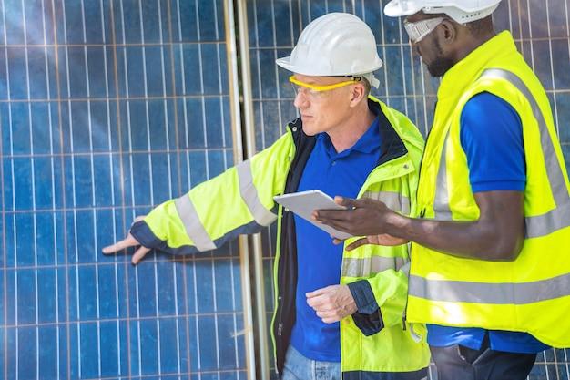 Trabalhadores da fábrica mostrando e verificando o painel de células solares para tecnologia sustentável