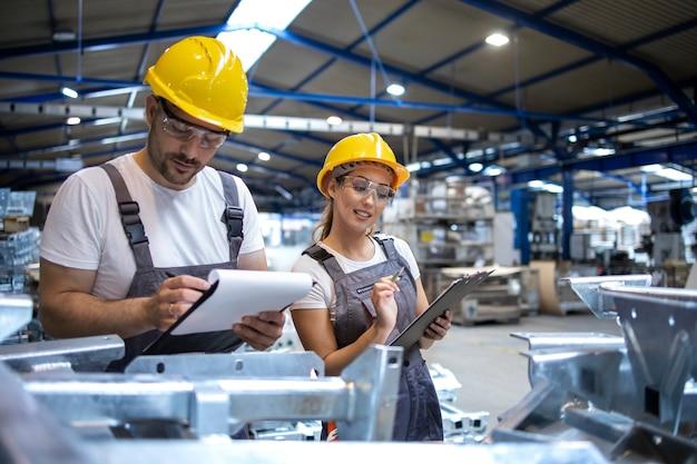 Trabalhadores da fábrica verificando a qualidade dos produtos em um grande salão industrial