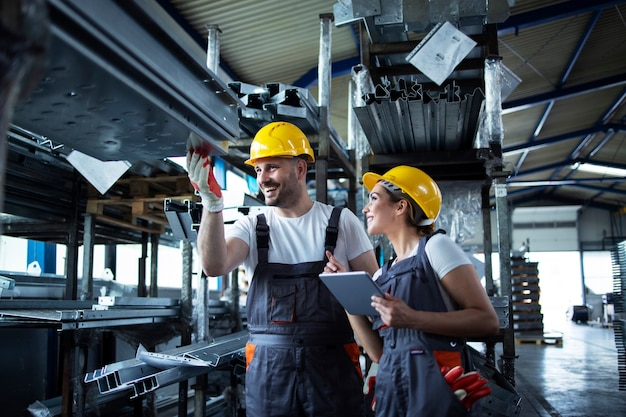 Trabalhadores da fábrica verificando o estoque com um tablet em um depósito industrial cheio de peças de metal