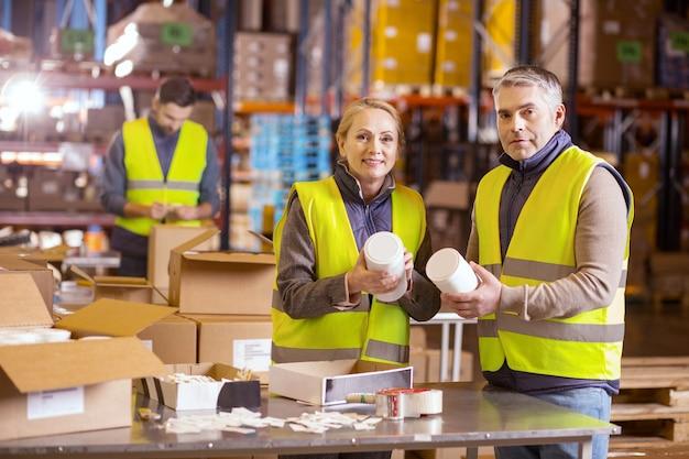 Trabalhadores da manufatura positivos vestindo uniformes especiais enquanto olham para você