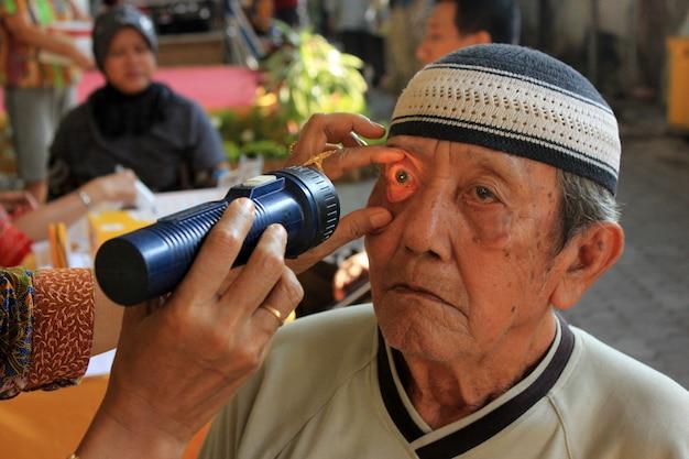 Trabalhadores da saúde estão verificando os olhos do paciente.