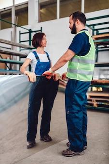 Trabalhadores de armazém carregando chapa de aço inoxidável inox na fábrica