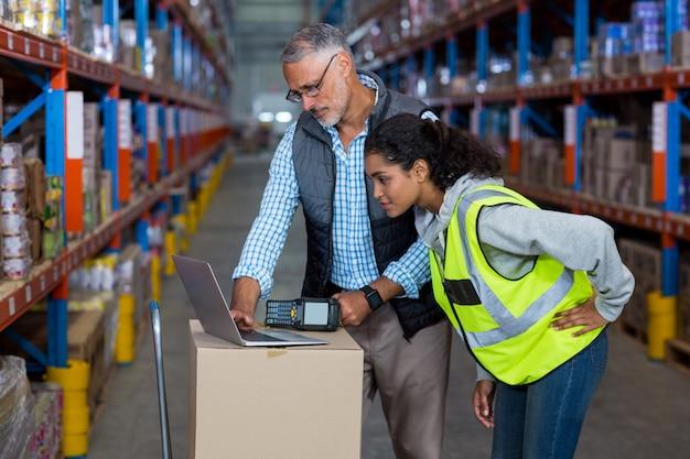 Trabalhadores de armazém discutindo com laptop
