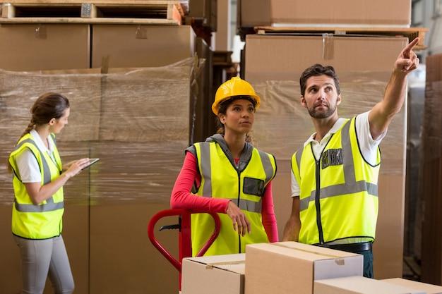 Trabalhadores de armazém discutindo enquanto preparava uma remessa