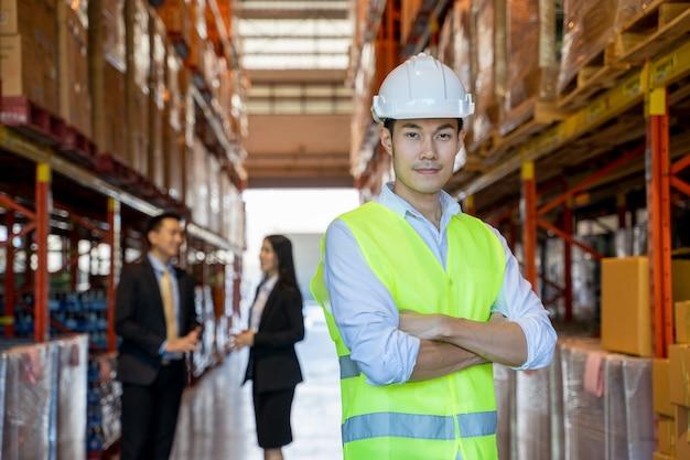 Trabalhadores de armazém em armazém com gerentes, trabalhador de armazém, sorrindo em um grande armazém.