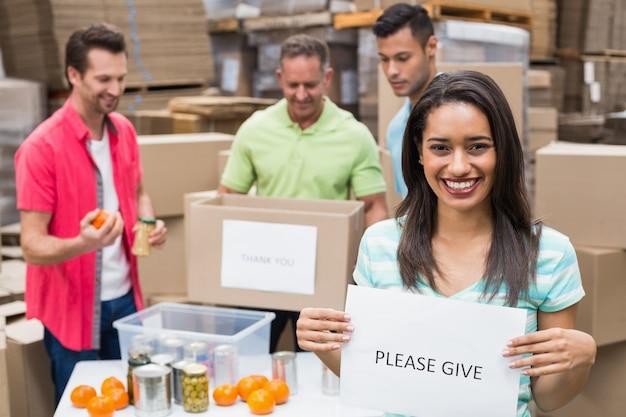 Trabalhadores de armazém que embalam caixas de doações