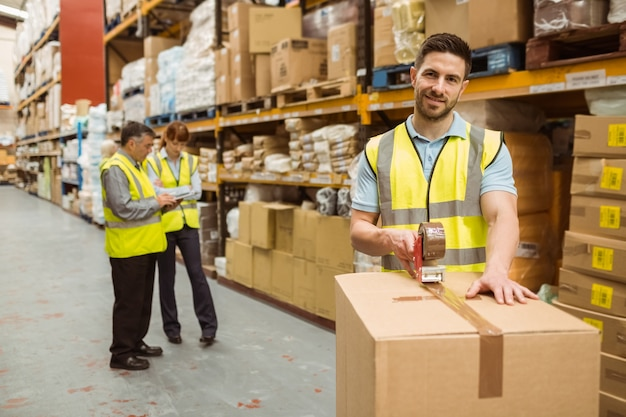 Trabalhadores de armazém sorridentes que preparam uma remessa