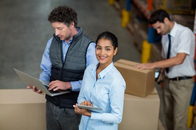 Trabalhadores de armazém usando laptop e tablet digital