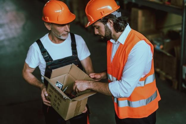 Trabalhadores de armazém, verificação de mercadorias em caixa de papelão