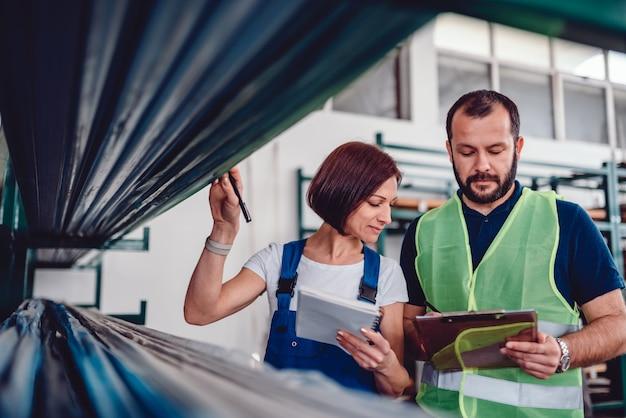 Trabalhadores de armazém, verificando a lista de pedidos