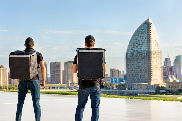 Trabalhadores de correio permanente com mochila, frente vista da cidade