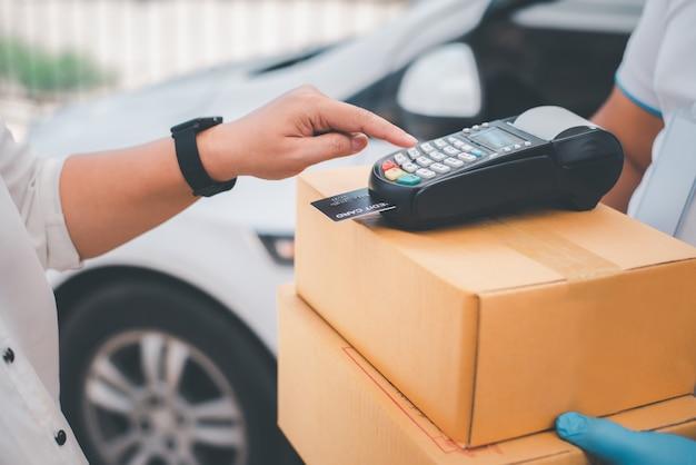 Trabalhadores de entrega do sexo masculino usam rostos higiênicos e luvas, entregam mercadorias ou encomendas, serviço de entrega para os usuários pagarem com cartão de crédito para conveniência e perdão durante a gravidez19.