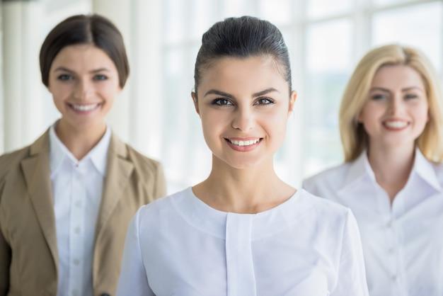 Trabalhadores de escritório feminino em pé na fila e sorrindo