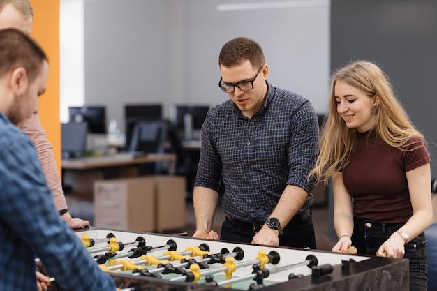 Trabalhadores de escritório jovem jogando futebol de mesa