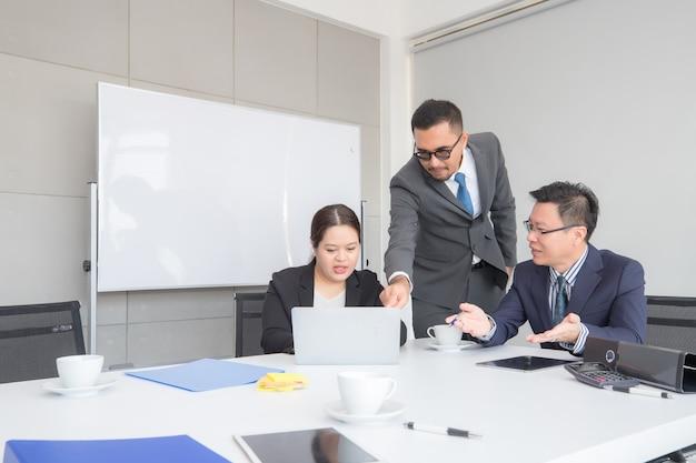 Trabalhadores de escritório masculinos e femininos sentam, olham para computadores e discutem.