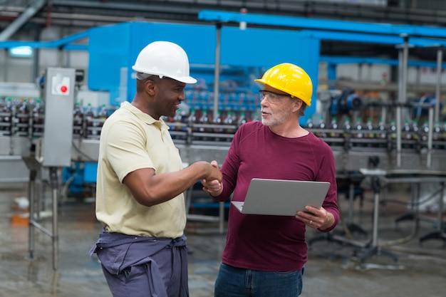 Trabalhadores de fábrica com laptop, apertando as mãos com seu colega