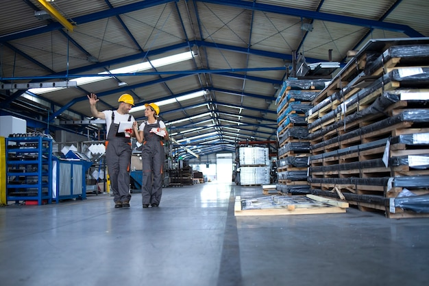 Trabalhadores de fábrica com roupas de trabalho e capacetes amarelos caminhando pelo hall de produção industrial e compartilhando ideias sobre organização
