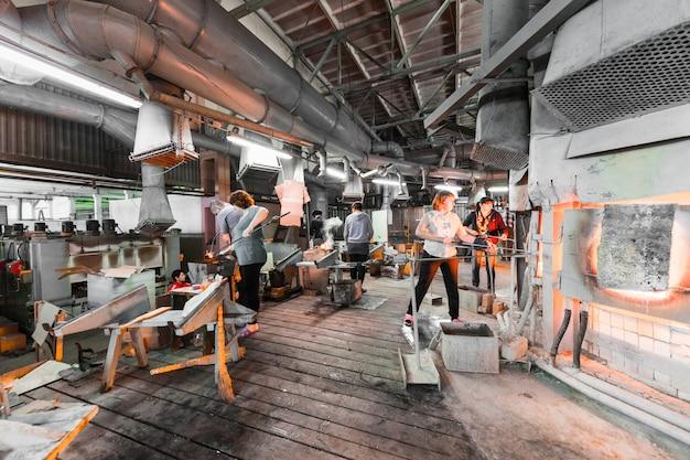 Trabalhadores de fábrica de vidro na produção de fundo de vidro trabalhando com equipamentos de fabricação