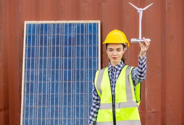 Trabalhadores de fábrica ou engenheiros segurando um modelo de moinho de vento no painel solar,
