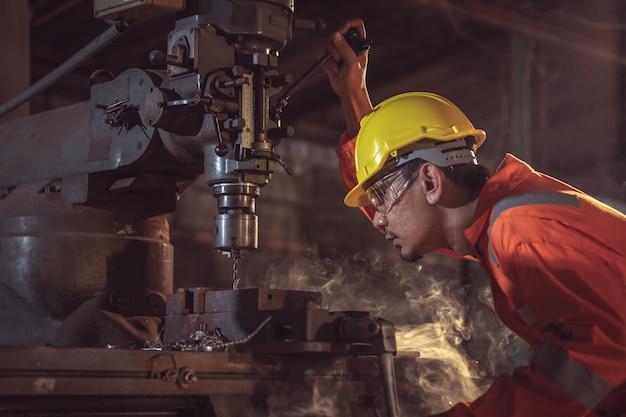 Trabalhadores de fábrica usam roupas de trabalho alaranjadas e óculos para impedir que pedaços de metal penetrem uniformemente com segurança