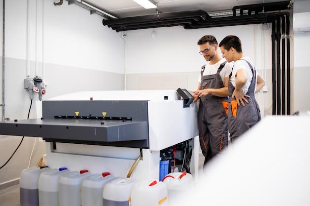Trabalhadores de impressão operando computador para máquina de chapa na gráfica