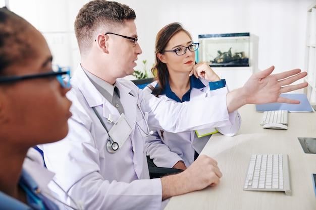 Trabalhadores de laboratório discutindo dados de pesquisa
