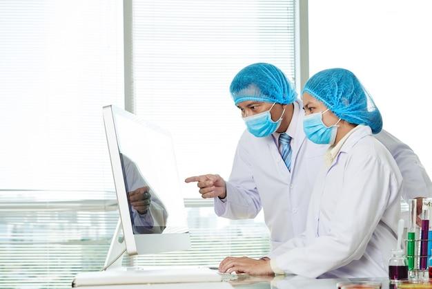 Trabalhadores de laboratório discutindo detalhes de pesquisa