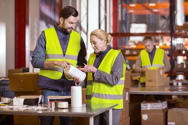 Trabalhadores de manufatura alegres e simpáticos juntos enquanto fazem o trabalho na fábrica