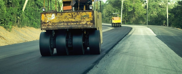 Trabalhadores de máquinas de construção de estradas dirigindo veículos de manutenção de estradas