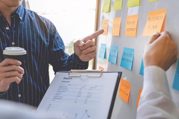 Trabalhadores de negócios jovem postando com lembretes adesivos autocolantes lembretes brainstorming criativo a bordo do colega em um espaço de trabalho moderno.
